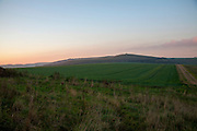 Chalk downland landscape at dusk with red sky from setting sun view to Milk HiIl, Alton Barnes, Wiltshire, England, UK