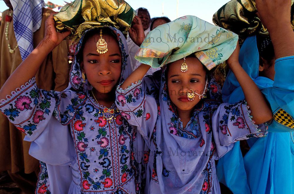"""Pakistan - """"Shiddis """", esclaves de l'empire des Indes - C'est à Mango Pir, mausolée d'un saint soufi du XIII éme siècle, situé à l'extérieur de Karachi que cette communauté noire, tiraillée entre ses racines africaines animistes et son identité musulmane pakistanaise, se retrouve et s'épanouit. Ils campent autour du mausolée dans des abris de fortune - Pendant quatre jours, des milliers de Shiddis venus de tout le sud du Pakistan, festoient, dansent, chantent, prient ensemble - Tous les jours, suivant des rites immuables venus de la nuit des temps, des groupes de Shiddis vont en dansant jusqu'au bassin aux crocodiles pour rendre hommage aux sauriens sacrés, gardiens et protégés de Mango Pir. Ici deux fillettes mènent la procession et portent sur leur tête les offrandes (viandes, fleurs et poudres) pour le crocodile. // Pakistan. Young Shiddi girl, the black of Pakistan with African origine."""