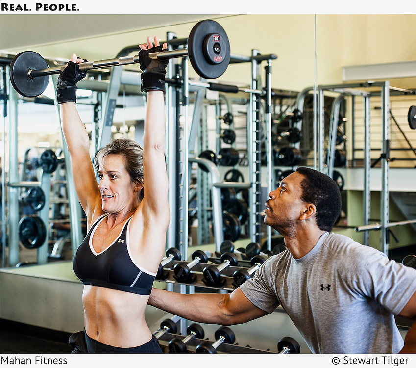 Fitness trainer working with athlete in a gym.