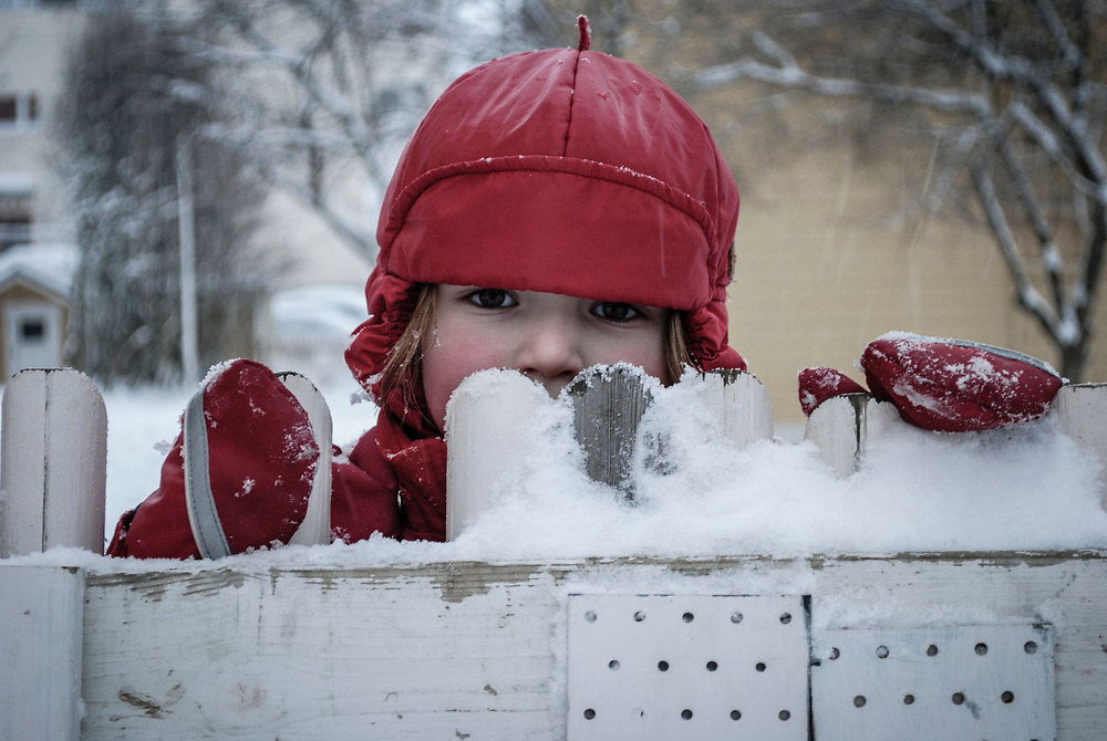 A young Finnish girl peaks over the fence in the middle of a frigid winter