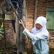 CAPTION: Dwi collects water from the household well. Since biopores have been installed at the house and throughout the wider community, Dwi's family has seen a notable increase in the water level. LOCATION: Dwi Wijayanti's house, Jl. St. Badaruddin II No 56, Bandar Lampung, Indonesia. INDIVIDUAL(S) PHOTOGRAPHED: Dwi Wijayanti.
