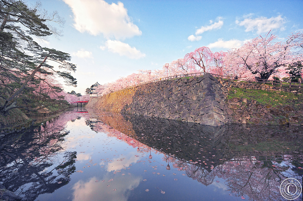 Hirosaki Castle Japan.A beautiful capture of the castle with a blue sky and the clouds reflecting on the water of the moat.<br />