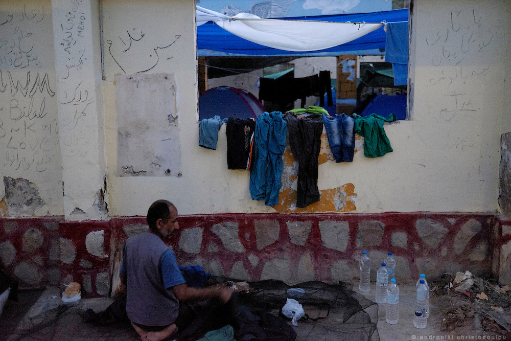 Old man organizing his spot for the night.<br /> Moria refugee camp is a bit further out of Mytilene city and it is divided in two sections. The inner part is well organised with buildings and police guarding it, and the outer part where mainly Afghan refugees live in tents and is purely guarded with chaotic situations, mainly during food distribution, frequently occur.