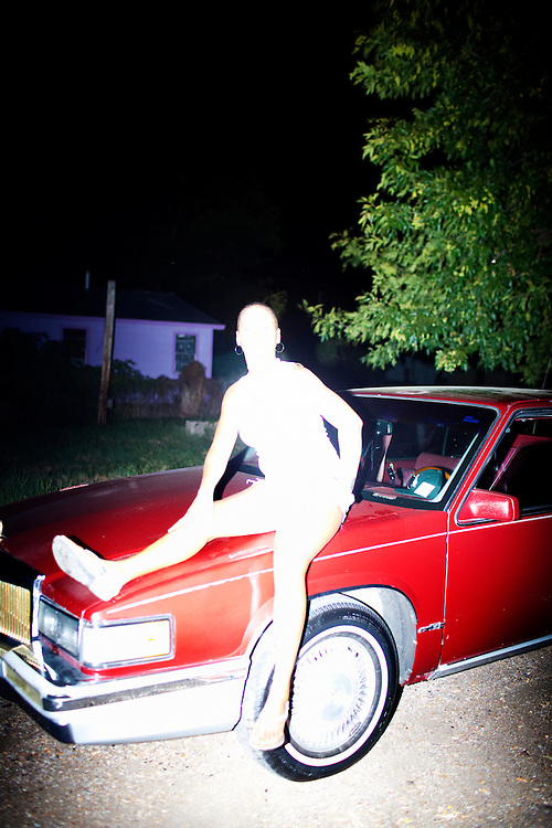A young woman strikes an open-legged pose on the hood of a car as a group of young men cat call her in the Baptist Town neighborhood of Greenwood, Mississippi on September 23, 2010.