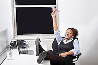 Relaxed businesswoman throwing paper airplane in office