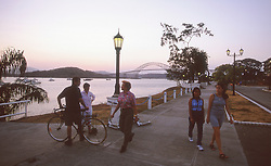 Locals out for a stroll along the Avenida Balboa Malecon on the Bahia de Panama (Panama Bay) leading to Panama City, Panama, Central America.