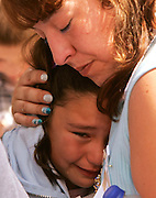 A family member of a victim in the World Trade Center attack comforts a young girl at the site of the disaster on the fourth anniversary of the attack in New York September 11, 2005.