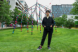 "© Licensed to London News Pictures. 16/07/2020. LONDON, UK.  London-based, Irish artist Eva Rothschild poses at the unveiling next to her work ""My World and Your World"".  The new 16m high public sculpture in Lewis Cubitt Park in King's Cross resembles a lightning bolt, painted in black, purple, pink, orange, green and red stripes.  The coronavirus lockdown caused the April 2020 launch to be postponed, but the unveiling has been able to go ahead now that certain lockdown restrictions have been eased by the UK government.  Photo credit: Stephen Chung/LNP"