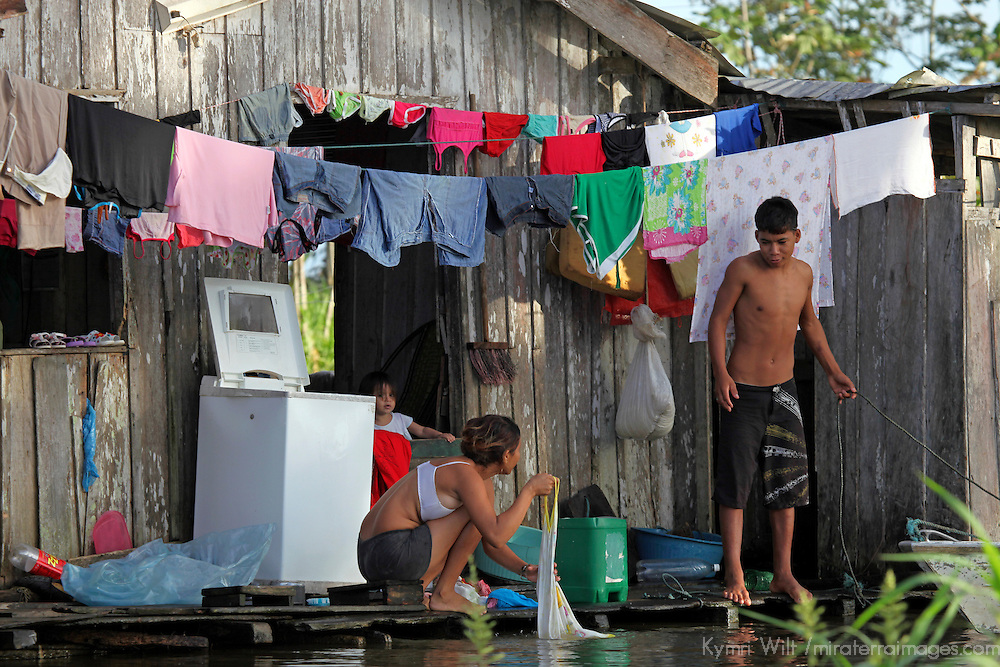 South America, Brazil, Amazon. A family sharing household laundry chores on the Amazon river.