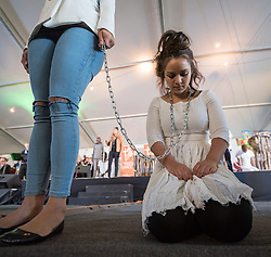 "13 May 2017, Windhoek, Namibia: Morning worship at the Lutheran World Federation's Twelfth Assembly, on the theme of ""Human Beings - Not for Sale"", illustrated by people bearing chains, enacted by Namibian dancers from the College of the Arts (COTA) in Windhoek, under direction of David Ndjavera and through choreography by Trixie Munyama. The Twelfth Assembly of the Lutheran World Federation gathers in Windhoek, Namibia, on 10-16 May 2017, under the theme ""Liberated by God's Grace"", bringing together some 800 delegates and participants from 145 member churches in 98 countries."