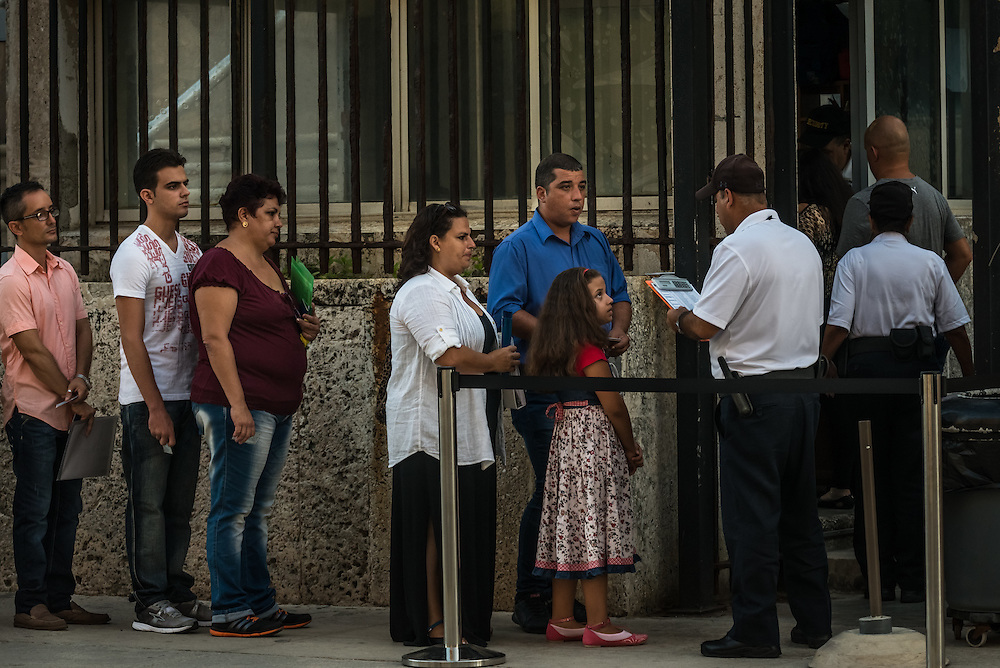HAVANA, CUBA - JULY 20, 2015: A family checks in with embassy security. Hundreds of Cuban nationals waited in line outside of the U.S. embassy to apply for visas on Monday morning. After more than half a century defined by mistrust and rancor, the United States officially reopened its six-story embassy in Havana today, marking a watershed moment of transition for the two countries as they lean toward closer diplomatic ties and ease past one of the last remnants of the Cold War.  President Barack Obama, when announcing an end to the diplomatic freeze, eased travel restrictions, opened the door for more remittances to Cuba and expanded the amount of goods that visiting Americans could bring back home – like Cuban cigars and rum. He even removed the country from the list of nations that sponsor terrorism. President Raul Castro, meanwhile, has spent the last five years, before the thaw even began with the Obama administration, attempting to alter his nation's economic dysfunction, ordering the firing of government employees, encouraging a slow but fresh influx of Cubans into self-employment and even creating a special economic zone in the coastal city of Mariel to attract foreign investment.  PHOTO: Meridith Kohut for The New York Times