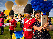 03 DECEMBER 2015 - BANGKOK, THAILAND: A Thai man takes a selfie of himself with a Thai soldier during the annual Trooping of the Colors Parade on Sanam Luang in Bangkok. The Thai Royal Guards Parade, also known as Trooping of the Colors, occurs every December before the celebration of the birthday of Bhumibol Adulyadej, the King of Thailand. The Royal Guards of the Royal Thai Armed Forces perform a military parade and pledge loyalty to the monarch. Historically, the venue has been the Royal Plaza in front of the Dusit Palace and the Ananta Samakhom Throne Hall. This year it was held on Sanam Luang in front of the Grand Palace.    PHOTO BY JACK KURTZ