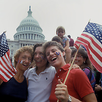Three women are among a patriotic crowd gathered in this undated (1980s) (4th of July) photo on the West Lawn of the U.S. Capitol in Washington, DC.