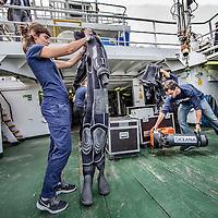 Nederland, Amsterdam, 7 juli 2016.<br /> Milieuclub Oceana ligt met haar onderzoeksschip Neptune in de Coenhaven van Amsterdam. Ze hebben geld gekregen van de postcodeloterij en gaan twee maanden op de Noordzee onderzoek doen hoe de visstand verbeterd zou kunnen worden.<br /> Op de foto: Het schip wordt klaargemaakt voor vertrek.<br /> Apparatuur wordt aan boord getakeld en geinstalleerd voor de wetenschappers aan boord van het schip, duikpakken worden gecontroleerd.<br /> <br /> Netherlands, Amsterdam, July 7, 2016.<br /> Environmental Club Oceana with her research vessel Neptune docked in the Coenhaven harbour of  Amsterdam. They have received money from the postcode lottery and will do research in the North Sea during two months to find out how fish stocks could be improved.<br /> On the photo: The ship is ready for departure.<br /> Equipment is hoisted aboard and installed for the scientists aboard the ship, diving suits are checked ..<br /> Foto: Jean-Pierre Jans