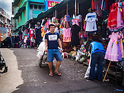 12 JANUARY 2017 - BANGKOK, THAILAND:        A porter pulls a bundle of clothes to a shop in Bo Bae Market. Bo Bae Market is a sprawling wholesale clothing market in Bangkok. There are reportedly more than 1,200 stalls selling clothes made in Thailand and neighboring countries. Bangkok officials have threatened to shut down parts of Bo Bae market, but so far it has escaped the fate of the other street markets that have been shut down.     PHOTO BY JACK KURTZ