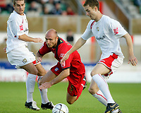 Photo: Marc Atkins.<br /> Milton Keynes Dons v Colchester United. Carling Cup. 22/08/2006. Wayne Brown of Colchester United is felled by MK Dons defenders.