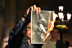 October 3, 2018 - Barcelona, Catalonia, Spain - A man seen burning a photo of the King of Spain Felipe VI during the protest..Hundreds of people gather at the Government headquarters of Catalonia hitting pans and burning photos of the King of Spain Felipe VI as they protest against the Spanish monarchy during the anniversary where his Majesty Felipe VI gave a speech against independence. (Credit Image: © Ramon Costa/SOPA Images via ZUMA Wire)