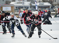 "Barry Enos from the Looney Bin takes control of the puck against The Dirty Lew's in the ""Just for Fun"" division during first round action on Meredith Bay for the New England Pond Hockey Classic Friday morning.  (Karen Bobotas/for the Laconia Daily Sun)"