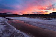 Dawn breaks over a basin of rivulets winding through salt flats, Death Valley National Park