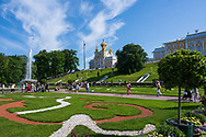 Peterhof, Russia -- July 21, 2019. Wide angle photo of the Summer Palace in Peterhof and a  fountain, the gardens and tourists behind it.