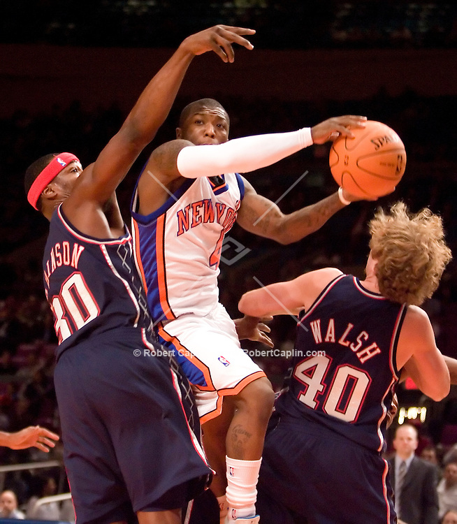 New York's Nate Robinson makes a pass between a pair of defenders in the first quarter of the New York Knicks vs New Jersey Nets match-up at Madison Square Garden Friday, Oct. 13, 2006.  Robert Caplin For The New York Times<br />