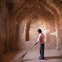 in Mandu India man sweeping ruins