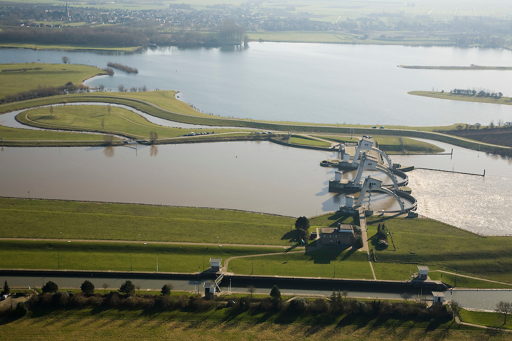 Nederland, Gelderland, Maurik, 11-02-2008; stuw in de rivier de Neder-Rijn, dient om waterpeil in de rivier te reguleren; de vizierschuif van de stuw is gesloten, hierdoor is er verschil in waterhoogte, dit verval wordt gebruikt om een waterkrachtturbine aan te drijven - de waterkrachtcentrale is het lage gebouw achter de stuw; de meanderende waterloop - met bocht, boven de stuw, is een vistrap (of vispassage) waardoor vissen de gesloten stuw stroomopwaarts kunnen passeren; onder in beeld de schutsluis voor de scheepvaart; de recreatieplas die hoort bij het Eiland van Maurik boven in beeld, linksboven de kerkspits van Maurik; neder rijn, watersport, sluiskolk, schutten, sluis. luchtfoto (toeslag); aerial photo (additional fee required); .foto Siebe Swart / photo Siebe Swart