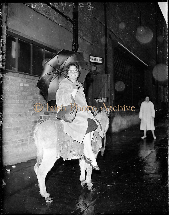 """Bus Fares Up"" .1960..15.01.1960..01 15 1960..15 January 1960...With an imminent rise in bus fares on the cards Maureen Potter,Ireland's best known entertainer, expressed her outrage by getting her own mode of transport, a donkey...Image shows Maureen leaving the Gaiety Theatre aboard her donkey."