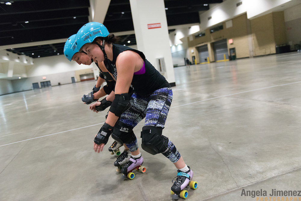 Fannie Tanner (Megan Gronau), left, and Sampson (Chrissy Sampson) of the Minnesota RollerGirls All-Star team warm up with one-on-one defensive drills at the start of practice in Exhibit Hall B at the Saint Paul RiverCentre in Saint Paul, Minnesota on November 3, 2015. <br /> <br /> The team is preparing to compete in, and host, the 2015 International WFTDA Championships at the Legendary Roy Wilkins Auditorium here in Saint Paul, Minnesota from November 6-8, 2015. <br />  <br /> Photo by Angela Jimenez for Minnesota Public Radio www.angelajimenezphotography.com