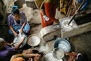 Women dehusking rice by hand. This activity is usually done in groups with long wooden sticks that act as pestles. The same sticks are also used to create  percussive music that help time their pounding to a rhythm. In the left corner women are sifting rice flour that are used to make cakes.