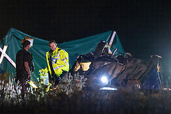 © Licensed to London News Pictures . 21/07/2014 . Nottinghamshire , UK . A police officer looks inside an overturned car at the scene . Police , fire crew and ambulances on the A1 road in Ranby yesterday morning (21st July 2014) following a fatal multi vehicle accident . Leroy and Sheila Carrington (aged 68 and 58) died at the scene when the Peugot 206 they were driving collided with a Vauxhall Astra . Roderick Franks (58) , who was a passenger in the Astra , died in hospital , following the crash . The road was closed in both directions whilst police investigated the scene .  Photo credit : Joel Goodman/LNP