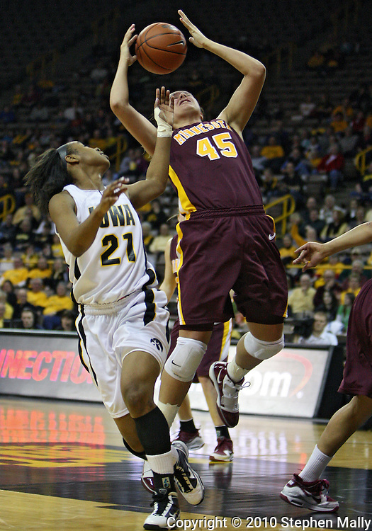 February 18, 2010: Iowa guard Kachine Alexander (21) and Minnesota forward Jackie Voigt (45) try to grab a rebound during the first half of the NCAA women's basketball game at Carver-Hawkeye Arena in Iowa City, Iowa on February 18, 2010. Iowa defeated Minnesota 75-54.