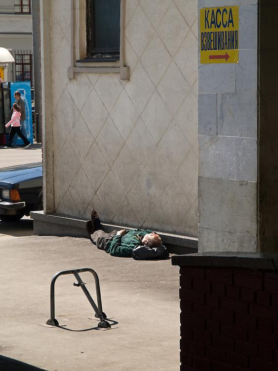 Schlafender Mann an der R&uuml;ckseite des Kasaner Bahnhofs (Kasanski woksal) welcher einer der neun Bahnh&ouml;fe in Moskau ist. Er liegt am Komsomolskaja-Platz, in unmittelbarer N&auml;he zum Jaroslawler und dem Leningrader Bahnhof, und ist bis heute einer der gr&ouml;&szlig;ten Bahnh&ouml;fe der russischen Hauptstadt. <br /> <br /> Sleeping person on the backside of the Kazansky Rail Terminal (Kazansky vokzal) which is one of eight rail terminals in Moscow, situated on the Komsomolskaya Square, across the square from the Leningradsky and Yaroslavsky terminals.