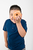 Pre-teen (10-12) boy holding doughnut over eye
