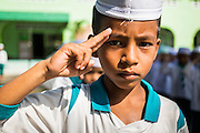 10 JULY 2013 - PATTANI, PATTANI, THAILAND: A Thai boy scout salutes at a private Muslim school in Pattani, Thailand. Many Muslim parents prefer to send their children to Muslim private schools because they are safer (public schools have been attacked by Muslim insurgents), the Muslim schools teach an Islam centric curriculum and teach what many in Pattani consider a more accurate version of Pattani history.   PHOTO BY JACK KURTZ