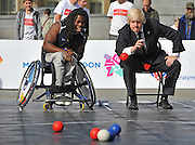 CENTRAL LONDON Pictured (L-R) Ade Adepitan and Boris Johnson. To celebrate two years to go until the 2012 Paralympic Games begin in London, the Mayor and Paralympians try their hand at the unique Paralympic sport of Boccia.  Played on a full size Boccia court in Trafalgar Square,the game, similar to bowls, was created especially for athletes with severe disabilities. .  23 August 2010. STEPHEN SIMPSON..