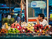 24 FEBRUARY 2016 - BANGKOK, THAILAND:   A man sells fruit from a street stall in front of Pak Khlong Talat in Bangkok. Bangkok government officials announced this week that vendors in Pak Khlong Talat, Bangkok's well known flower market, don't have to move out on February 28. City officials are trying to clear Bangkok's congested sidewalks and they've cracked down on sidewalk vendors. Several popular sidewalk markets have been closed in recent months and the sidewalk vendors at the flower market had been told they would be evicted at the end of the month but after meeting with vendors and other stake holders city officials relented and said vendors could remain but under stricter guidelines regarding sales hours. The flower market is one of the best known markets in Bangkok and has become a popular tourist destination.      PHOTO BY JACK KURTZ