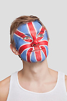 Thoughtful young Caucasian man with British flag painted on face against white background