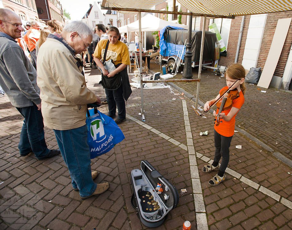 Een man geeft geld aan de viool spelende Oskar op de vrijmarkt in Utrecht tijdens Koninginnedag 2012.<br /> <br /> A young girl is playing the violin at the flee market on Queensday in Utrecht.