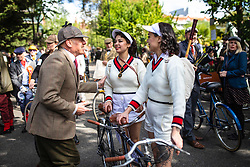 © Licensed to London News Pictures. 04/05/2019. London, UK. A man speaks with two women wearing vintage tennis outfits at the start of the annual Tweed Run bicycle ride, in which participants cycle around the capital wearing vintage tweed outfits. Photo credit: Rob Pinney/LNP
