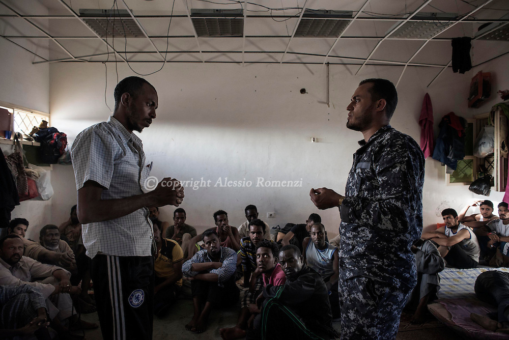 Libya, Misurata district: an illegal workers accused of being clandestine is seen inside an overcrowded cell at Al Kararem detention center as he begs a Libyan guard to be putted in touch with his family which does not know that is now in jail, on May 16, 2015. Alessio Romenzi