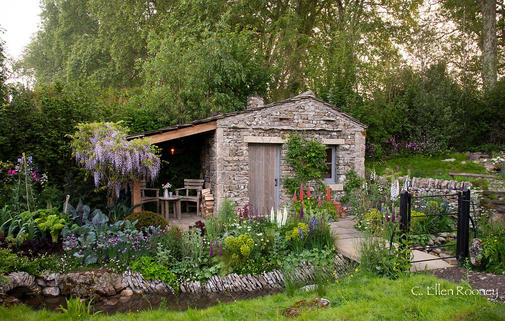 A traditional cottage garden surrounding a stone bothy in the Welcome to Yorkshire Garden at the RHS Chelsea Flower Show 2018, London, UK