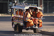 A group of young monks ride in the back of a tuk-tuk in Pakse, Laos. Tuk-tuks are a primary mode of transportation in this southern Lao city that is the gateway to the Bolivan Plains coffee plantation area.