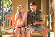 Father and daughter sitting together on a porch swing after a day of fishing at Billingsley Creek Lodge and Retreat, Hagerman, Idaho. MR