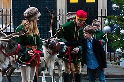 London, December 15th 2014. Children are given a treat as they visit Downing Street for a Christmas party when they are greeted by reindeer at the entrance to Number 10.