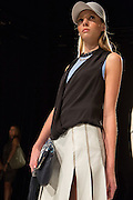 A short skirt in off white with a black wrap sleeveless top worn over a sleeveless powder blue T. By Monika Chiang at Spring 2013 Fashion Week in New York.