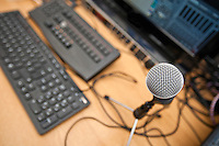 Microphone and computer keyboards on table at television studio