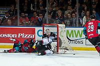 KELOWNA, CANADA - MARCH 16:  Schael Higson #21 of the Kelowna Rockets slides into the net of David Tendeck #30 after a crosscheck by Jared Dmytriw #22 of the Vancouver Giants on March 16, 2019 at Prospera Place in Kelowna, British Columbia, Canada.  (Photo by Marissa Baecker/Shoot the Breeze)