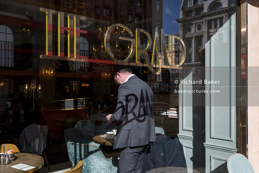 Seen from through the window, a male customer prepares to leave his place in Le Grand cafe on Piccadilly, the shadow of its name, an elegant and prestigious place to eat and drink in Mayfair, imprinted on his back, on 6th March 2020, in London, England.
