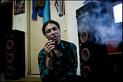 """Chabbo, 32 years old, transvestite by the age 17, smokes a cigarette. Asked if feels more man or women can not give a certain answer. Chabbo shares a common apartment with other transvestites. He his the Guru for all the members in the building where they live. Transvestites people have created a community, a kind of an hierarchical staircase, based on rules handed down by generations. Night in Lahore, Pakistan on Monday, Dicember 01 2008... Afternoon in Lahore, Pakistan on Tuesday, December 02 2008.....""""Not men nor women"""". Just Hijira, Kusra. Painted lips, Kajal surrounding their eyes and colourful veils..Pakistan is today considered a strongly, foundamentalist as well, islamic country. But under its reputation, above all over the talebans' continuos advancing, stirs a completely extraneous world, a multiethnic mixed society. Transvestites make part of it, despite this would not be admitted by a strict law. Third gender, the Hijira are born as men (often ermaphrodites) or with an ambiguous genital situation, and they have their testicles and penis removed through a - often brutal - surgical operation. The peculiarity is that this operation does not contemplate the reconstruction of a female organ. This is the reason why they are not considered as men nor women, just Hijira. They are often discriminated, persecuted  and taxed with being men prostitutes in the muslim areas. The members of this chast perform dances during celebrations, especially during weddings, since it is anciently believed that an EUNUCO's dance and kiss in the wedding day brings good luck to the couple's fertility...To protect the identities of the recorded subjects names and specific .places are fictionals."""